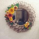 Pensou um desse bem na entrada. Esse é um espelho simples enfeitado com flores de feltro e rolinhos de papel higienico cortados.